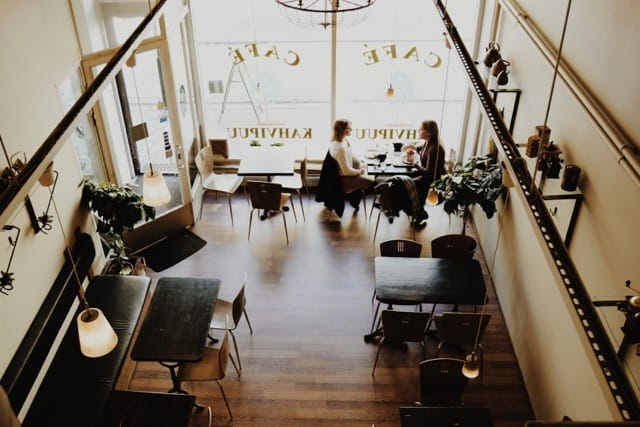 aerial-view-of-cafe-with-girlfriends-sitting-at-table-and-talking